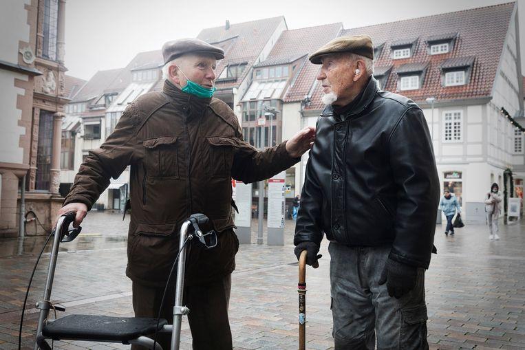 Bruno Knorr (l), een 88-jarige inwoner van Lemgo, praat met een vriend over corona. Knorr is niet bang voor een prik: 'We zullen er heus niet van omkiepen.' Beeld Daniel Rosenthal / de Volkskrant