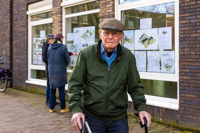 Oud voorzitter harmonie Kunst Adelt Chris Willems is tevreden over de presentatie van de drie plannen oude Dr. Landmanschool bij de ramen van Helvoirt Thuis, voorbijgangers kunnen op hun gemak de plannen bekijken.