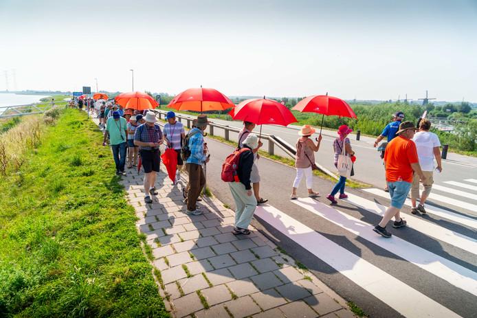 Drukte op de dijk. Een groep toeristen komt van boord van hun cruiseschip en wordt begeleid door een vrijwilliger van de Stichting Werelderfgoed Kinderdijk (SWEK). ,,Op naar de molens!''