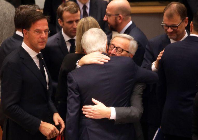 Jean-Claude Juncker omarmt Brexit-onderhandelaar Michel Barnier. Beeld EPA