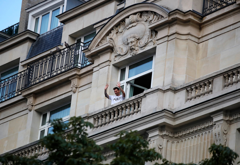 De Argentijnse voetballer Lionel Messi zwaait naar fans vanaf een balkon van het Le Royal Monceau-hotel in Parijs. Hij tekende dinsdag een contract bij Paris Saint-Germain. Beeld Reuters