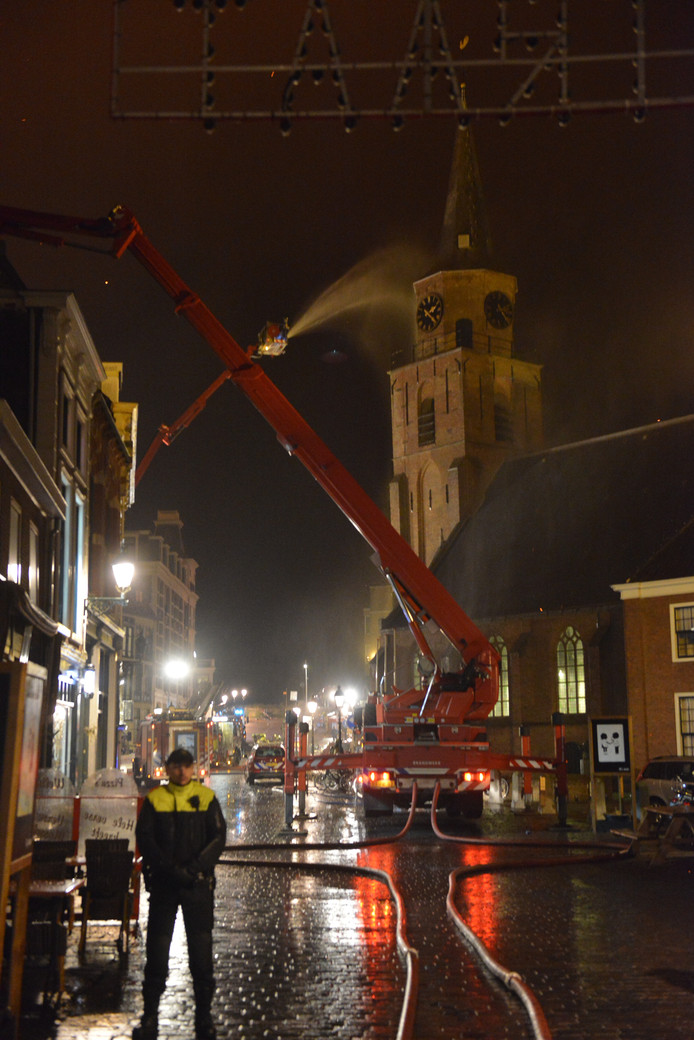 De brandweer probeert de kerktoren nat te houden zodat de brand niet overslaat.