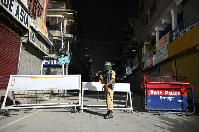 Een Indiase paramilitair bij een wegafsluiting in Srinagar, Kashmir, waar de spanningen steeds verder oplopen.  Beeld AFP