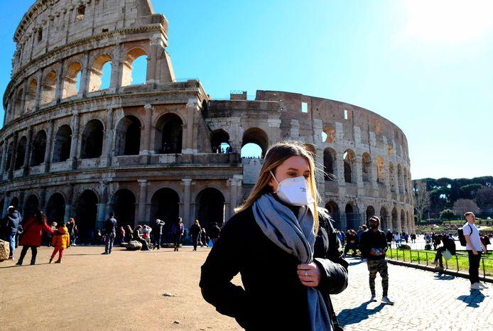 Une femme portant un masque devant le Colisée, à Rome.
