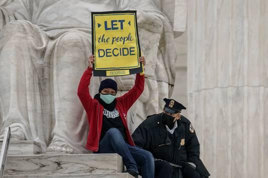 Een demonstrant voor de Senaat wordt weggehaald door de politie.