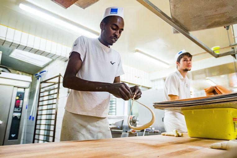 Een Nigeriaanse asielzoeker loopt stage bij een bakkerij in Reutlingen, Duitsland. Beeld Getty Images