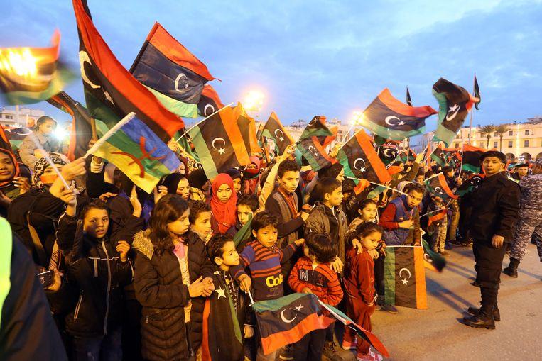 Libische vrouwen zwaaien met de nationale en de Berberse vlag. Beeld AFP