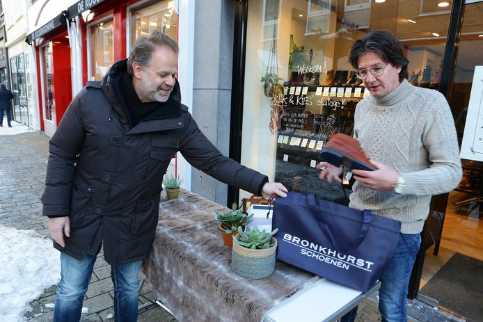 Roel Bronkhorst laat een klant nog even een paar schoenen zien. Winkeliers mogen weer open in Gorinchem, maar wel op afspraak.