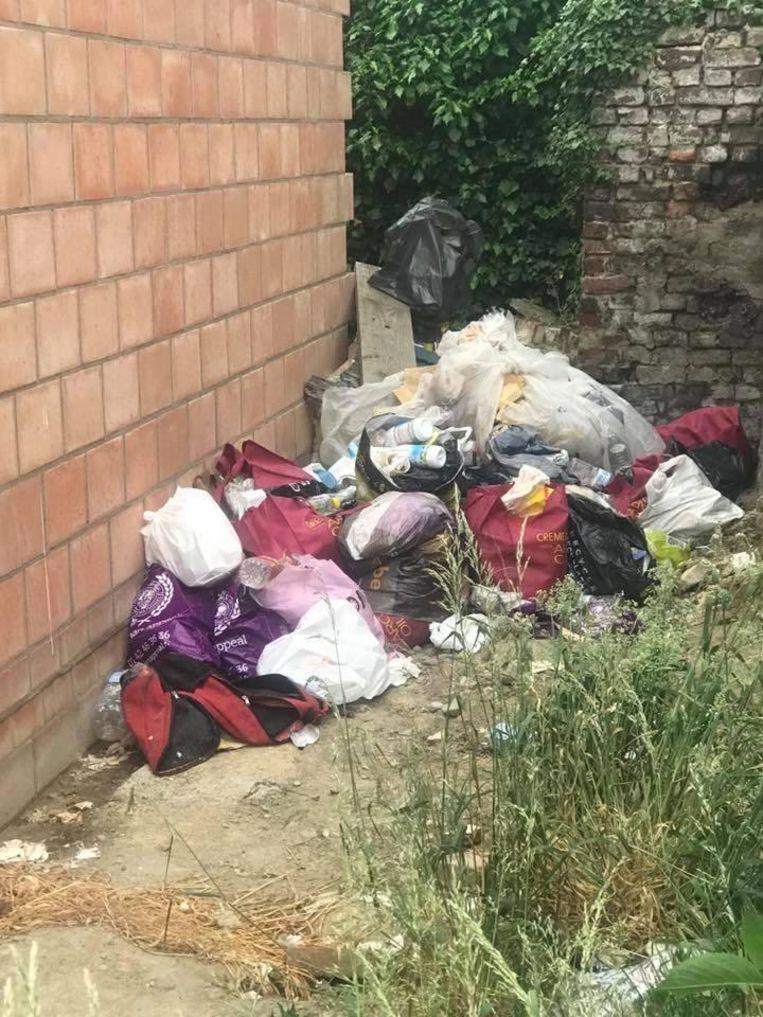 Het vuilnis ligt op een hoop in de tuin.