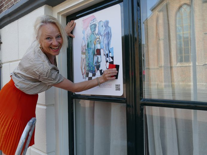 Dianne Ploemen plakt een kunststicker op het raam van het stadhuis.