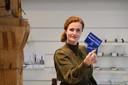 Monique Otto met de Hengelo Kadokaart, met daarop het beeldmerk van Hengelo.