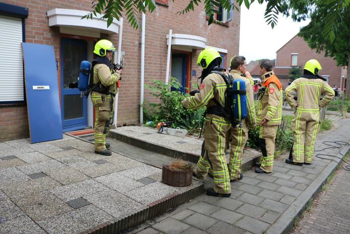 Brandweermannen staan voor de woning.