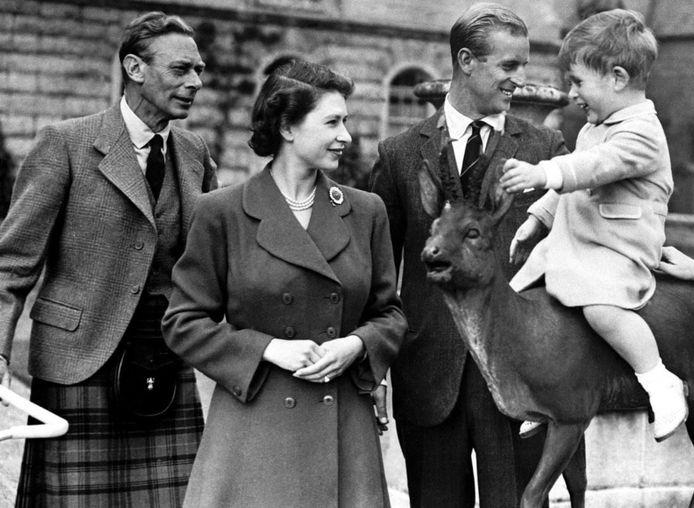 Queen Elizabeth met links haar vader koning George VI en rechts haar echtgenoot prins Philipp en de kleine prins Charles.