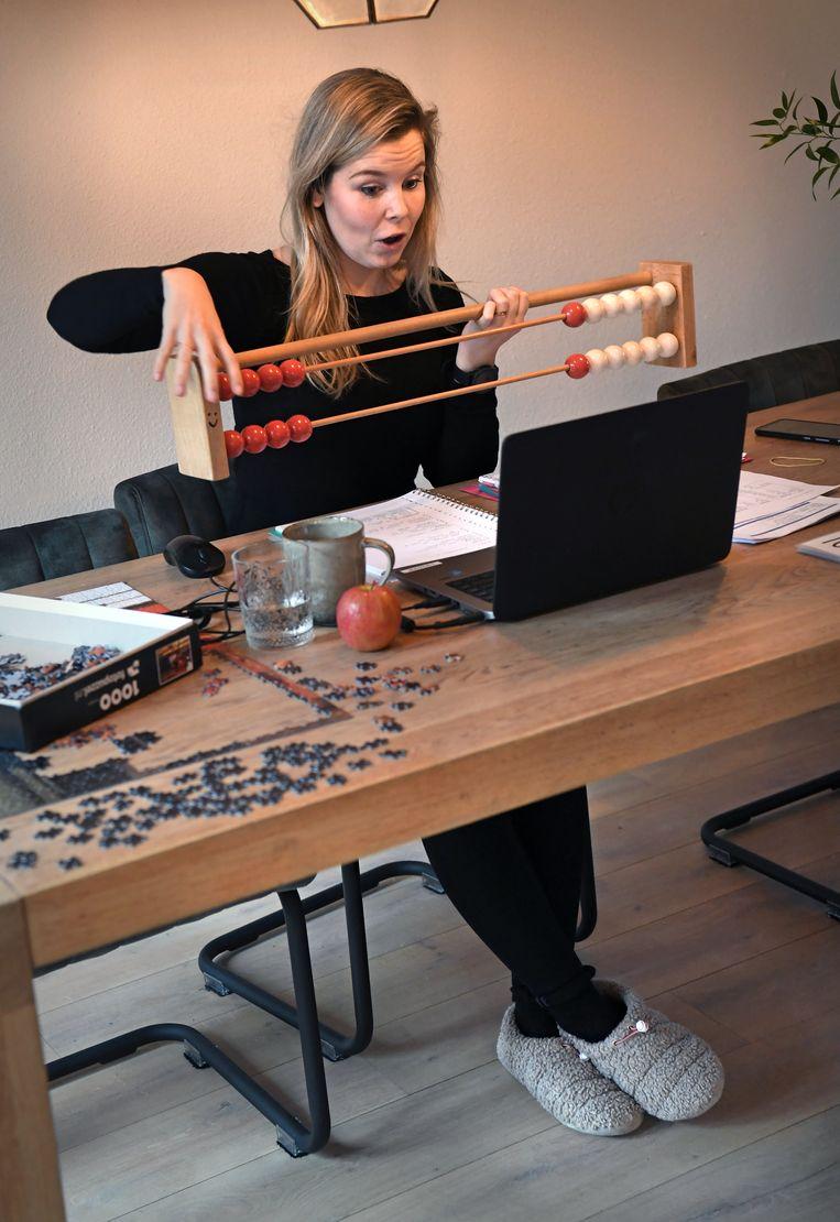Leerkracht Liesanne van Tiem geeft groep 3 van basisschool OBS De Wijzer in het Gelderse Beneden-Leeuwen vanuit huis rekenles.  Beeld Marcel van den Bergh / de Volkskrant
