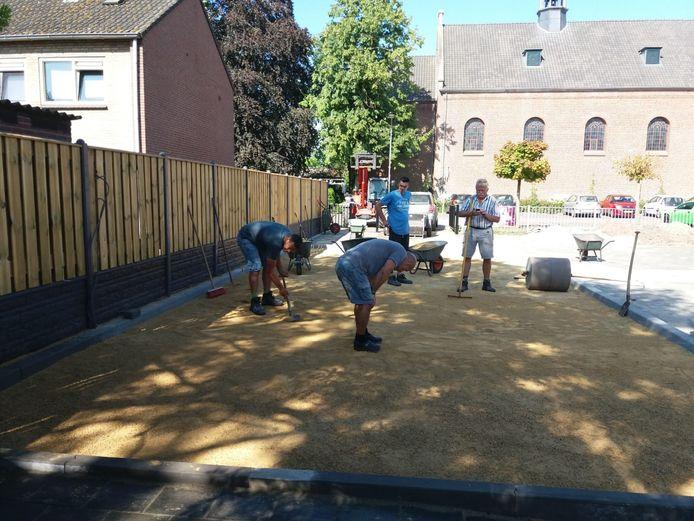 De vrijwilligers werken in de hete zon aan de aanleg van een dubbele jeu-des-boulesbaan in Langeweg
