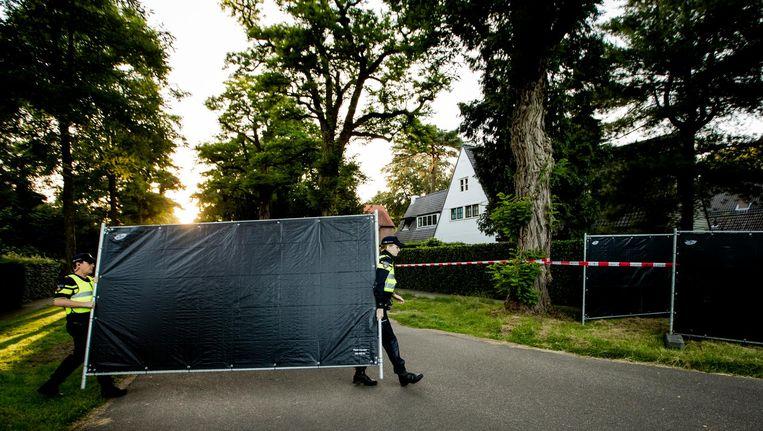 Agenten verplaatsen hekken bij het huis van Koen Everink voorafgaand aan de reconstructie van de moord op de zakenman. Beeld null