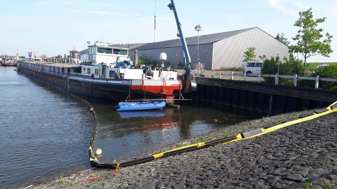 Rond de drugsboot Arsianco in Moerdijk ligt een scherm in het water. Dit moest voorkomen dat chemicaliën die uit het vol water gelopen ruim lekten, zich verder verspreidden.