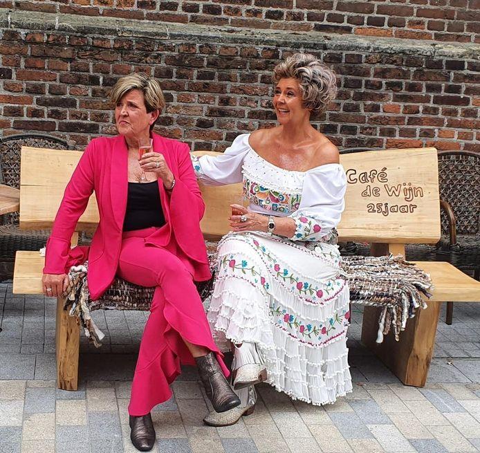 Jolanda (links) en Bernadette op het jubileumbankje dat ze van de vaste bezoekers van café De Wijn kregen.