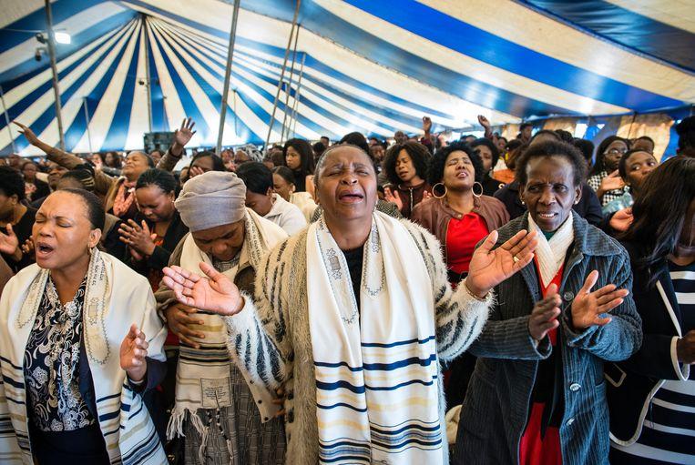 Duizenden kerkgangers bidden in een van de tenten van de Unity Fellowship Church in Soweto. Beeld Bram Lammers