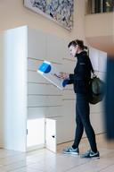 Een medewerker haalt haar pakketje uit het kluisje van de pakketwand van MyPUP.