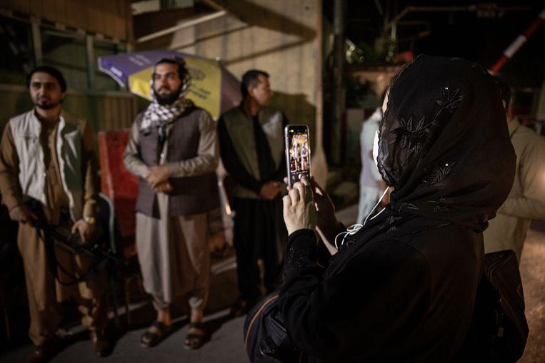Journaliste Zahra Nabi neemt foto's van Taliban bij een checkpoint in Kaboel. Beeld Hollandse Hoogte / The New York Times Syndication