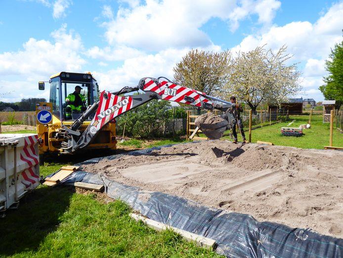 De gemeentedienst hielp bij de aanleg van de zandbak.