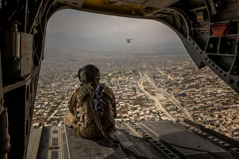 Een Amerikaanse militair kijkt vanuit een Chinook-helikopter uit over Kabul, begin mei. Beeld HH