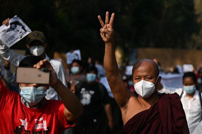 Een monnik in Yangon maakt het inmiddels traditionele gebaar met de drie opgestoken vingers.