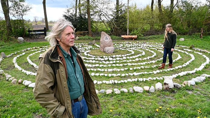 """Willem Hulsegge bij het door hem gemaakte labyrint in Dedemsvaart. Wendy is begonnen aan het pad, waarbij ze zich door het labyrint laat leiden naar de stilteplek in het midden. ,,Je gaat van buiten naar binnen, komt in het centrum en gaat dan weer van binnen naar buiten."""""""