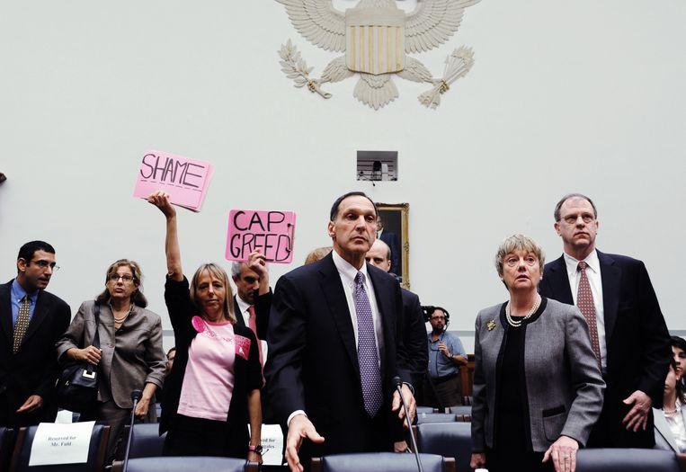 2008: actievoerders houden protestboren omhoog op het moment dat Richard S. Fuld Jr., topman van Lehman Brothers, zich opmaakt om te getuigen bij een hoorzitting in Washington over de val van zijn bank. Die leidde de wereldwijde financiële crisis in. Beeld AFP