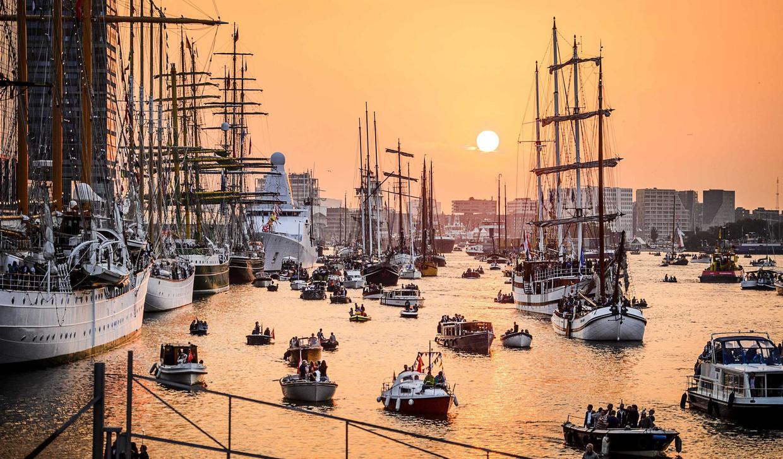 Tallships en pleziervaart op het IJ tijdens zonsondergang aan het einde van de eerste dag van Sail Amsterdam 2015.  Beeld Remko de Waal/ANP