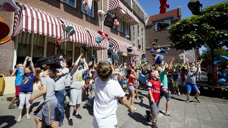 Leerlingen van basisschool Statenkwartier gooien gezamenlijk hun tas in de lucht bij het inluiden van de zomervakantie. Beeld anp