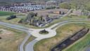 Luchtfoto van de locatie waar het politiecomplex in Meerhoven, Eindhoven moet komen. Gezien vanaf de N2/A2-afslag met op de voorgrond de turborotonde. Onderzocht wordt of de uitrit van het complex rechtstreeks daarop kan uitkomen. De Sliffertsestraat (langs de woningen) loopt nu nog dwars door de locatie. Die moet verlegd worden.