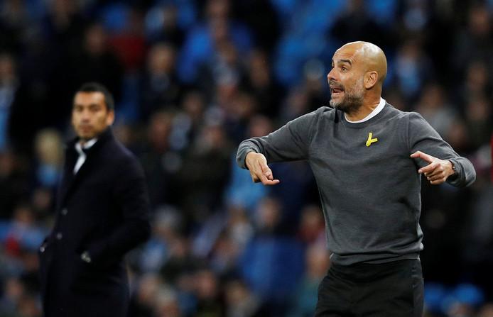Pep Guardiola zit er kort op bij Manchester City. Giovanni van Bronckhorst (l) kijkt toe.