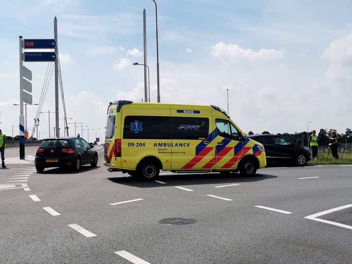 Hulpverlening na de aanrijding tussen een auto en een motor op de oprit van de snelweg A12 in Ede.