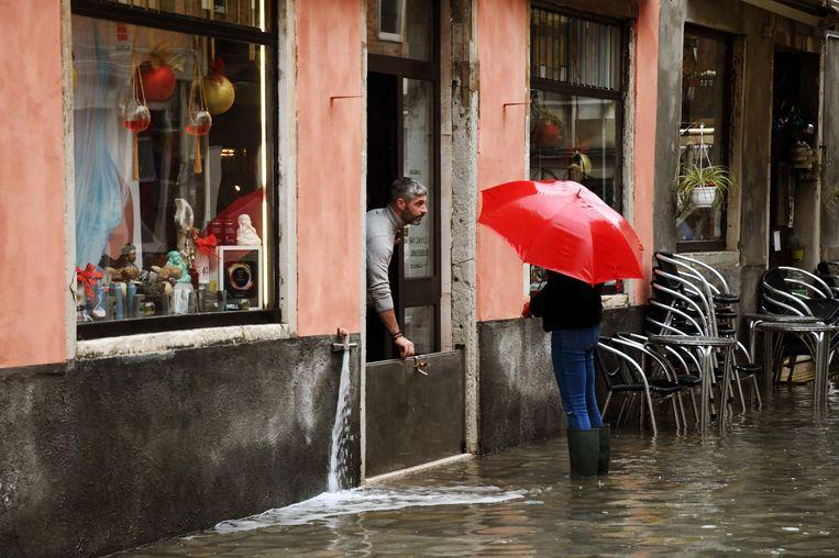 Een winkelier probeert het water tegen te houden dat naar binnen dreigt te stromen. Beeld AFP