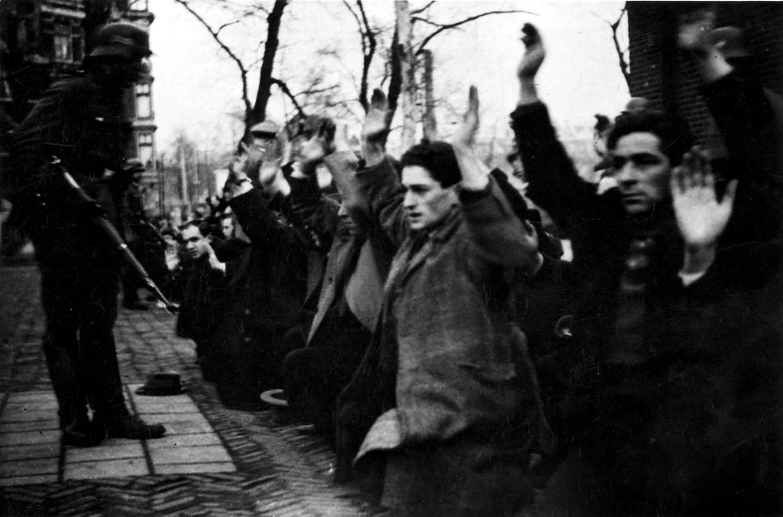 Geknielde Joden worden onder schot gehouden op het Jonas Daniël Meijerplein. De tweede van rechts is Meier Vieijra, één van de 427 joodse mannen die op 22 en 23 februari 1941 werden opgepakt op het plein.  Beeld Hollandse Hoogte / Spaarnestad Photo