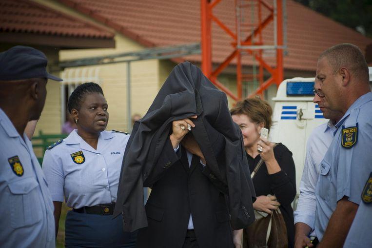 Pistorius bedekt zijn gezicht bij aankomst bij de rechtbank. Beeld getty