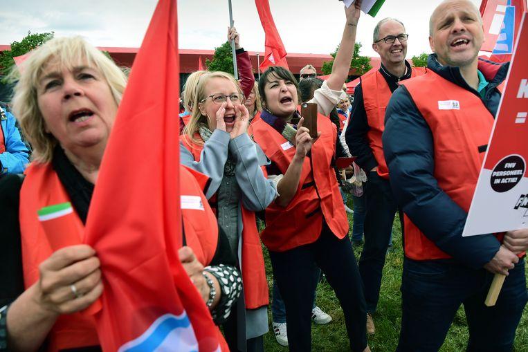 Personeel van vakbond FNV houdt een protestbijeenkomst op een grasveld voor het hoofdkantoor. Beeld null
