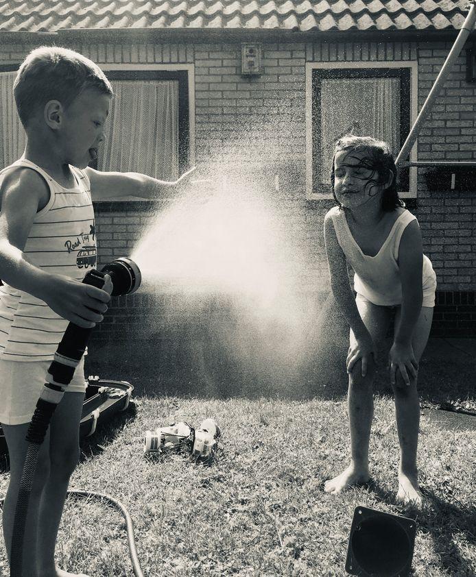 AFKOELING Na de sportdag van school begin juli hebben de kinderen Elise en Tom heerlijke waterpret in de tuin.
