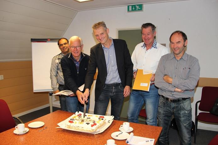 Wethouder Erik Volmerink snijdt de taart aan om het heugelijke feit te vieren.