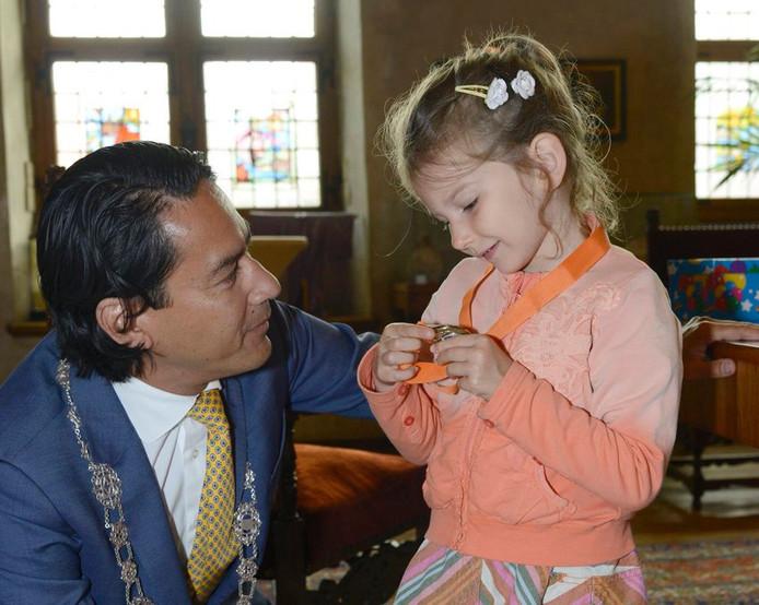 Rosa bekijkt medaille die ze van burgemeester Harald Bergmann kreeg omgehangen.