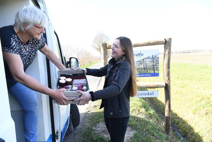 Hanneke Versteijnen van TerraVie in Loon op Zand reikt Mieke Aerts van Goei Eete de bestelde producten aan.