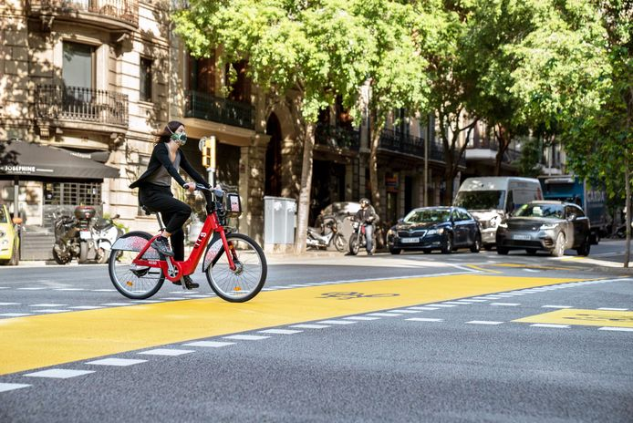 Spaanse vrouw draagt mondmasker op fiets, Barcelona