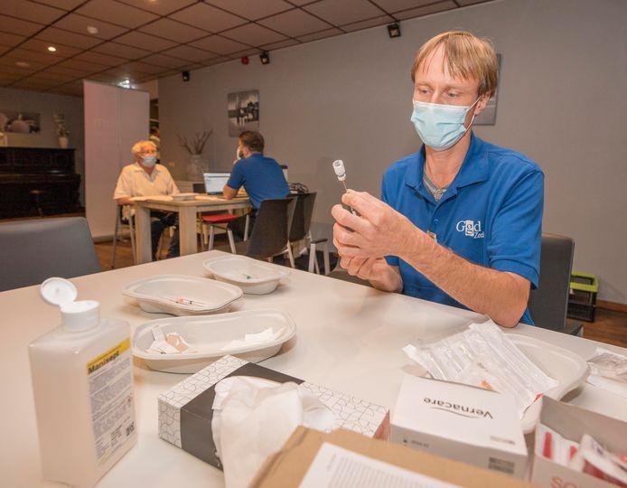 Vaccinatie Rilland. Medewerker GGD Zeeland trekt het Pfizervaccin op en Pieter Seghers  kijkt op de achtergrond toe.