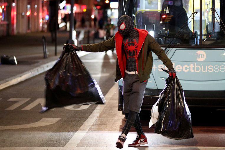 Vuilniszakken wegbrengen in Spider-Man-outfit tijdens een demonstratie in New York, ook naar aanleiding van de dood van George Floyd.  Beeld Justin Heiman / Getty