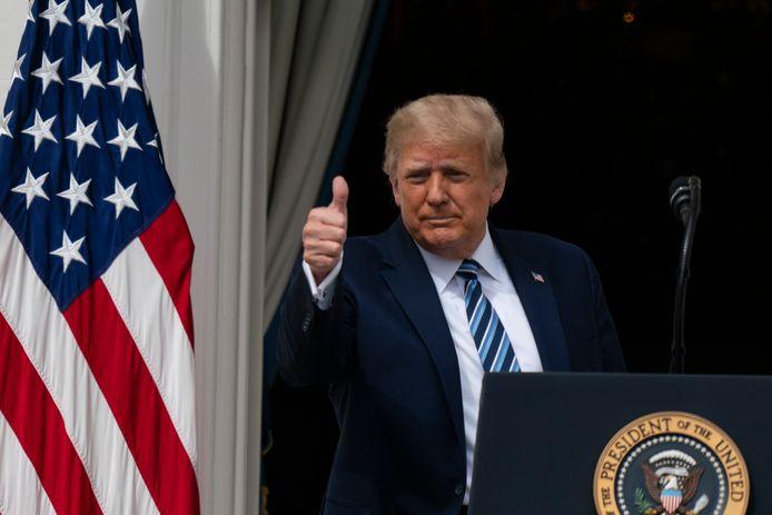 Trump steekt zijn duim op bij zijn eerste publieke toespraak sinds zijn besmetting vanaf het balkon van het Witte Huis.