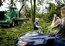 Een vrouw haalt bladeren van haar auto, een dag na de hevige storm.