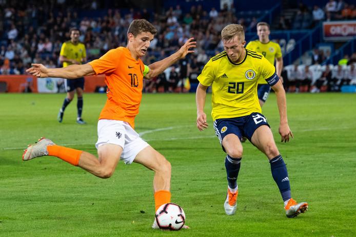 Jong Oranje-captain Guus Til probeert voor te geven, Jong Schotland-captain Ross McCrorie probeert dat te voorkomen.