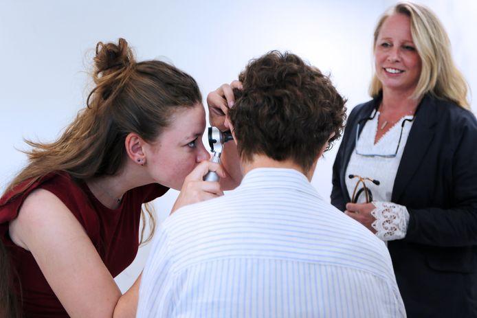 Huisarts Lonneke Reedijk (r.) in Roosendaal kijkt toe terwijl doktersassistente Destiny Zijderveld (22) de oren controleert bij een patiënte.